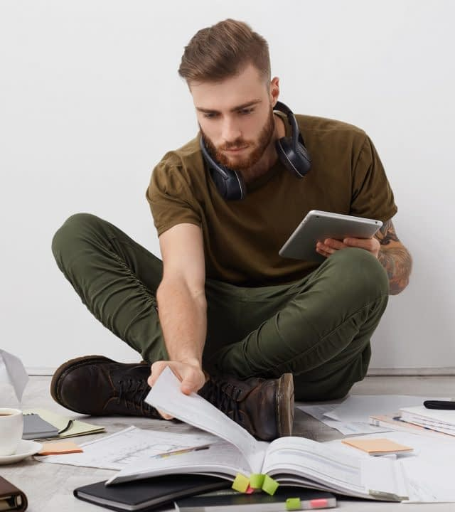 Preoccupied beared male college student with trendy hairdo looks attentively into book, holds modern tablet, works on making report, surrounded with many papers, being involved in process of studying.